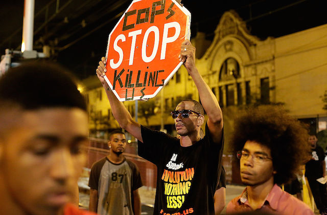 Protesters hold cardboard stop signs that implore cops to