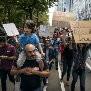 """A man carries a child on his shoulder as he walks down a closed-off street in New York City. The child is holding a sign that says """"No human is illegal."""" Behind them, protestors hold up protest signs that say things like """"Keep the kids, deport racists."""""""