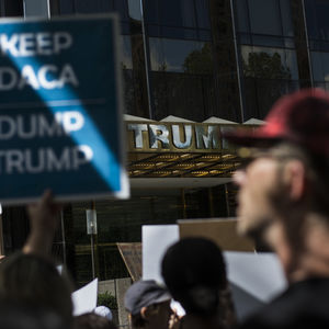 """A sign is blurred in the foreground that says, """"Defend DACA, Dump Trump."""" In the background the Trump International Hotel is in focus."""