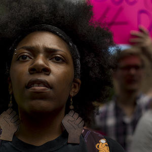 Close-up shot of a Black woman. Behind her, a protestor holds up a pink protest sign.