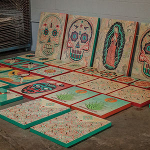 Colorful paintings of Mexican sugar skulls lay on a storeroom floor