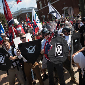 White male Vanguard American members wearing sunglasses and brandishing flags and shields with White supremacist symbols