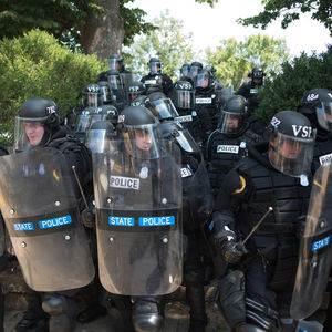 A group of state police is riot gear amass