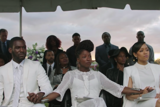 Black man and two Black women dressed in white sitting at a graveside funeral service