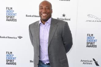 Black man in grey blazer and purple shirt with blue jeans against white wall and blue carpet