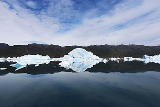Calved icebergs from the nearby Twin Glaciers are seen floating on the water on July 30, 2013, in Qaqortoq, Greenland. Greenland loses, on average, 375 gigatons of ice per year, according to a new report.