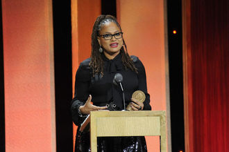 Black woman in black dress holds gold award statue behind brown podium with black microphone in front of orange and black wall