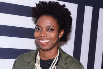 Black woman in green jacket with black sweater and beige necklace in front of black-and-white-striped wall