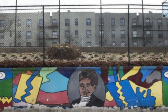 Mural of Black man in black-and-white clothing by blue, red, yellow, brown, grey and green color blocks on grey wall in front of black fence and brown apartment buildings
