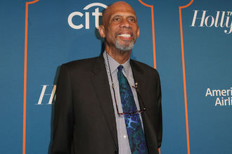 Black man in black suit with black-and-white shirt and blue-green tie in front of blue background with white text and orange outline