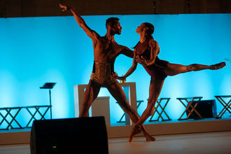 Black man and woman in gold and black performance outfits on brown wood stage in front of light blue screen and black and white furniture