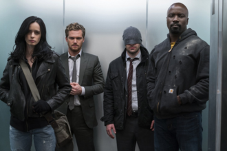White woman in black leather jacket and blue jeans next to White man in grey suit next to White man in grey suit and headwrap next to Black man in black hoodie in front of grey wall
