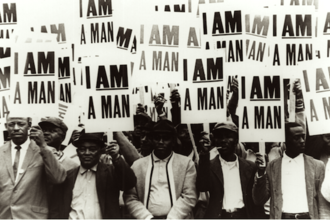 """A group of Black men on strike hold up signs that say """"I AM A MAN"""""""