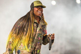 Black woman in green and grey baseball cap and green-brown campoflauge jacket and pants with multicolored patches holding black-and-white microphone in front of grey-lit background and scaffolding