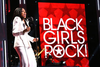 Black woman in white suit in front of black and red screen with white text