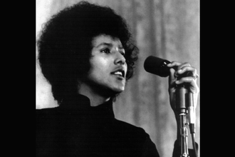 Black-and-white image of Black woman in black sweater behind grey microphone and stand in front of light grey wall