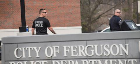 """Two police officers dressed in black stand behind a sign that says """"City of Ferguson Police Department."""""""