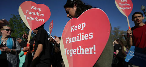"""Women in front of the U.S. Supreme Court hold up red, heart-shaped signs that say, """"Keep Families Together!"""""""