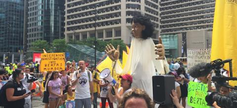 Activists around white-clothed Berta Cáceres puppet, wearing white shirts and waving yellow flags