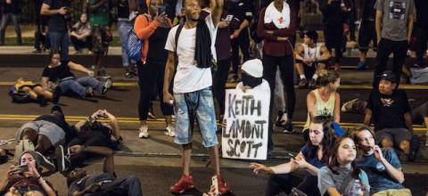 "Black man with fist raised surrounded by people on ground and white sign reading ""Keith Lamont Scott"" in black ink"