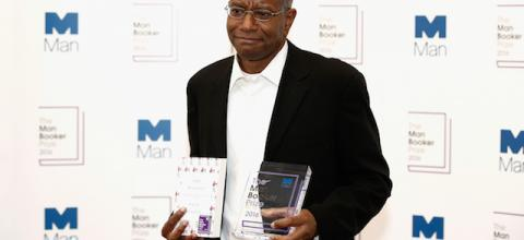 Black man in black suit with white shirt against white wall with blue logos and black text, holding white book with black lettering and transparent award with blue lettering