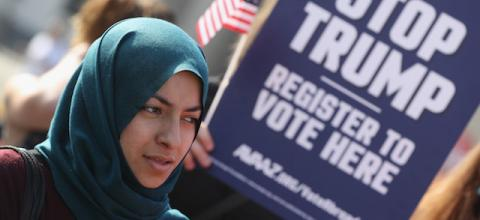 Woman in teal hijab and maroon shirt in front of navy sign with bold white text and red, white and blue American flag