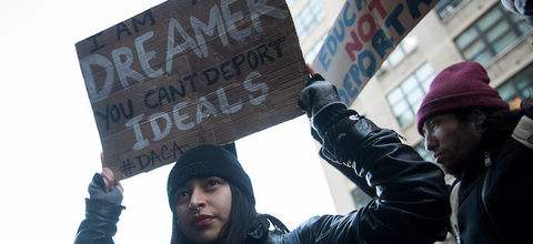 A young woman in a black hat protests immigration raids