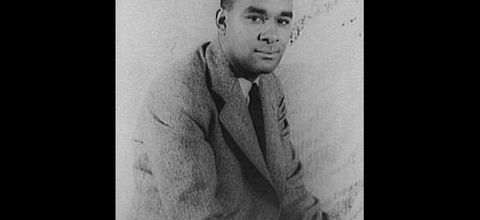 Black-and-white photo of Black man seated in light colored suit