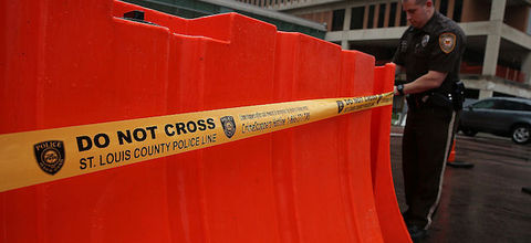 Yellow police tape against orange barrier