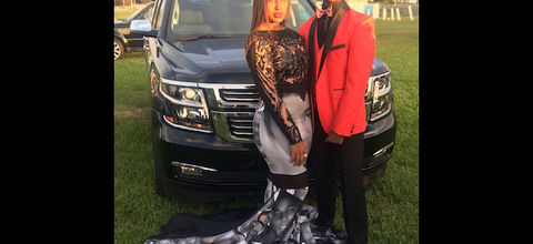 Black girl in black dress with grayscale images of Black women, men and children next to Black boy in red tuxedo with black pants in front of black car on green grass in front of grey sky