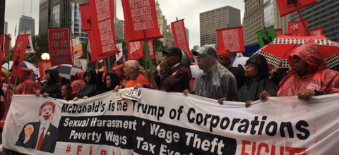 """Protestors hold sign that reads: """"McDonald's is the Trump of Corporations"""""""