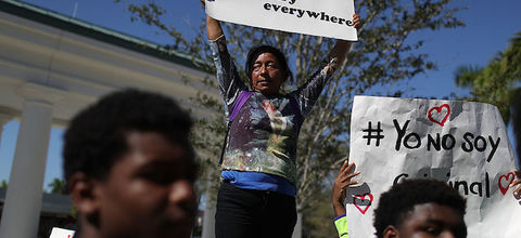 """Woman, flanked by young men, holds sign that reads: """"#SancturaryEverywhere."""""""