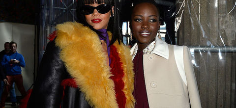 Black woman in black sunglasses and black, orange, red and purple outfit next to Black woman in beige jacket and maroon sweater in front of grey scaffolding and black wall