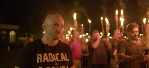 White man in black t-shirt near White men in multicolored clothing holding brown torches with orange flames in front of black night sky