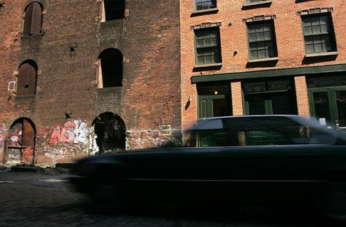 A car drives past a building that has been renovated beside one that is still derelict in Brooklyn, an area experiencing rapid gentrification on May 17, 2005, in New York City.