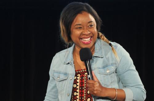 Phoebe Robinson in red patterned dress and blue denim jacket, holding black microphone