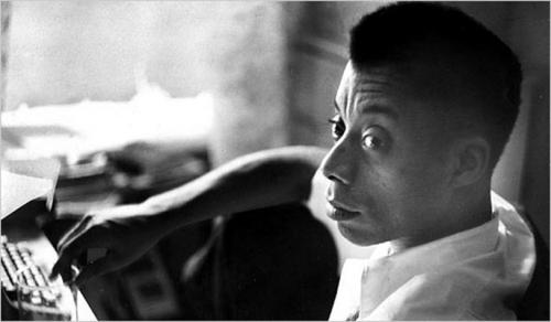 James Baldwin in black-and-white photo with white shirt and black pants
