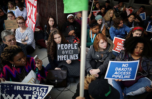 Hundreds of people sit in silent protest against the Dakota Access Pipeline outside the offices of the Army Corps of Engineers November 15, 2016. in Washington, D.C.