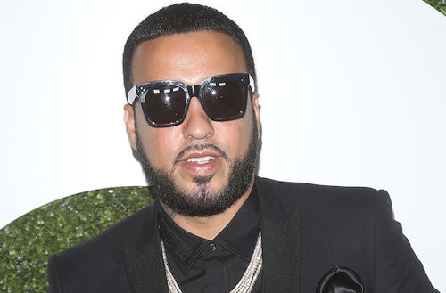 A light-skinned man wears a necklace and sunglasses on a red carpet