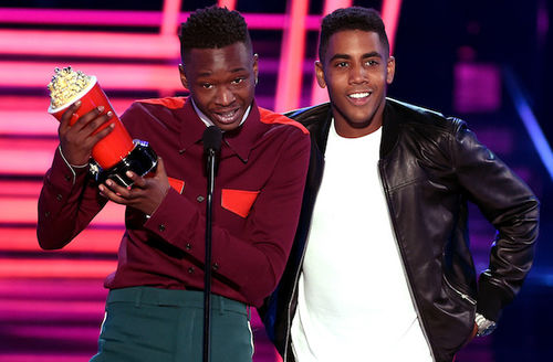 Black man in maroon shirt and green pants holds red-and-gold popcorn statue while speaking at black microphone next to Black man in white shirt and black leather jacket in front of neon pink-lit background