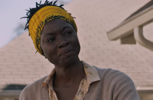 Black woman in yellow headwrap and brown sweater in front of brown house roof and blue sky