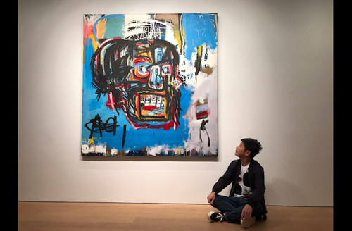 Asian man sits beneath blue painting with black, yellow, red and white features on white wall above brown floor
