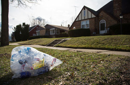 Trash bag full of water bottles sits in front of a home.