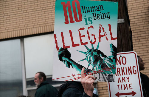 """Person holds sign that reads, """"No human being is illegal."""""""