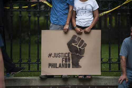 """A cardboard sign with a raised fist reads """"Justice for Philando."""""""