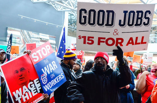 Black man in navy jacket and red hat holds red, white and blue sign next to Black people holding red, white and blue signs
