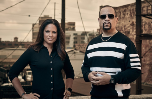 Brown woman in black shirt stands next to Black man in black-and-white-striped sweater in front of brown sky and cityscape