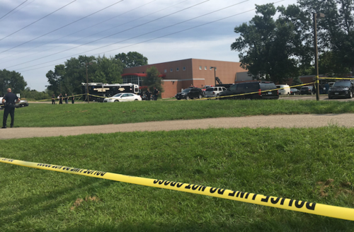Building surrounded by police tape and officers