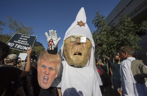 A protester wears a costume likeness of Sheriff Joe Arpaio as a member of the KKK with a picture of President Trump