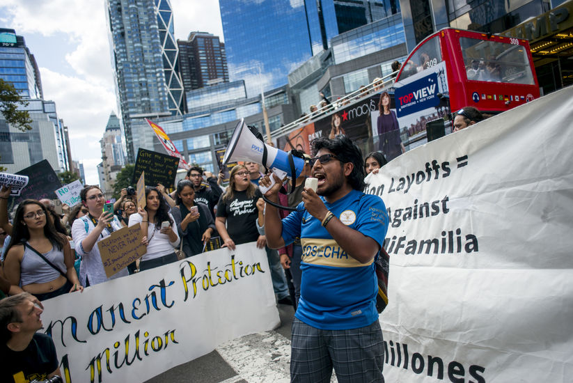 A Brown man in a blue shirt yells into a megaphone in a busy street. Activists surround him.
